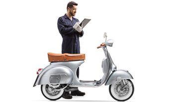 Motorbike mechanic in a uniform inspecting a scooter and writing a document isolated on white background